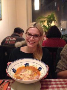 Glückliche Schwester mit Lasagne zum Reinlegen